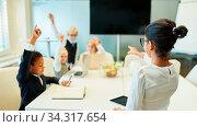 Lehrerin in einer Klasse oder im Seminar stellt Fragen an Schüler oder Studenten. Стоковое фото, фотограф Zoonar.com/Robert Kneschke / age Fotostock / Фотобанк Лори