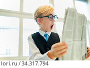 Kind als Geschäftsmann beim Lesen der Tageszeitung staunt mit offenem Mund. Стоковое фото, фотограф Zoonar.com/Robert Kneschke / age Fotostock / Фотобанк Лори
