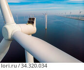 Close view with drone at windmill park in the lake Ijsselmeer in the netherlands Noordoostpolder, Windmill turbines from above in Europe producing green energy during global warming. Стоковое фото, фотограф Zoonar.com/Fokke Baarssen / easy Fotostock / Фотобанк Лори