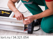Young male contractor repairing heater indoors. Стоковое фото, фотограф Elnur / Фотобанк Лори