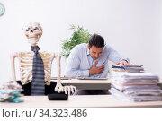 Купить «Young male employee and skeleton in the office», фото № 34323486, снято 31 октября 2019 г. (c) Elnur / Фотобанк Лори