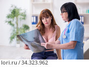 Young woman visiting old doctor oncologist in breast cancer. Стоковое фото, фотограф Elnur / Фотобанк Лори