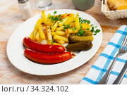 Roasted sausages with fried potatoes and pickled cucumbers. Стоковое фото, фотограф Яков Филимонов / Фотобанк Лори