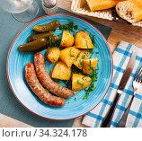 Купить «Appetizing sausages with potatoes and pickled cucumbers closeup», фото № 34324178, снято 3 августа 2020 г. (c) Яков Филимонов / Фотобанк Лори