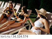 Female persons with coctails leisures on sunbeds. Стоковое фото, фотограф Tryapitsyn Sergiy / Фотобанк Лори