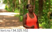 Купить «african woman with earphones and smart watch», видеоролик № 34325102, снято 10 июля 2020 г. (c) Syda Productions / Фотобанк Лори