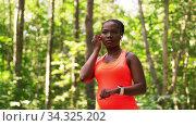 Купить «african woman with earphones and smart watch», видеоролик № 34325202, снято 10 июля 2020 г. (c) Syda Productions / Фотобанк Лори