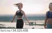 Two young smiling women doing aerobic exercises outdoors - jumping on one spot. Стоковое видео, видеограф Константин Шишкин / Фотобанк Лори