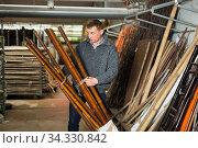 Man looking for bamboo poles at market. Стоковое фото, фотограф Яков Филимонов / Фотобанк Лори