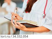 Ärztin oder Krankenschwester notiert Termine in einen Kalender oder eine Warteliste. Стоковое фото, фотограф Zoonar.com/Robert Kneschke / age Fotostock / Фотобанк Лори