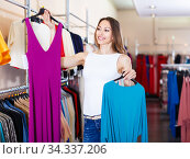 Купить «young cheerful brunette selecting new dress in fashionable showroom», фото № 34337206, снято 11 апреля 2017 г. (c) Яков Филимонов / Фотобанк Лори