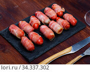 Sausage rolled with bacon on black dish. Стоковое фото, фотограф Яков Филимонов / Фотобанк Лори