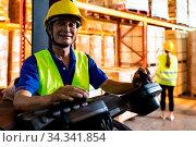 Portrait asian male warehouse worker using forklift truckin large... Стоковое фото, фотограф Zoonar.com/Vichie81 / easy Fotostock / Фотобанк Лори