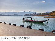 Khao Sok, Thailand, February 07, 2020: Lonely long Thai boat at the pier. Редакционное фото, фотограф Олег Белов / Фотобанк Лори