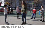Energetic kids playing and skipping on elastic jumping rope in european yard. Стоковое видео, видеограф Яков Филимонов / Фотобанк Лори