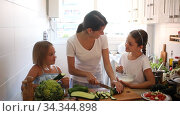 Cheerful woman with two little daughters prepare vegetable salad in the kitchen at home. Стоковое видео, видеограф Яков Филимонов / Фотобанк Лори