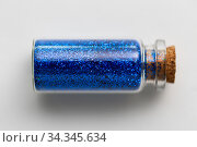 blue glitters in bottle over white background. Стоковое фото, фотограф Syda Productions / Фотобанк Лори