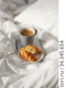 Купить «croissants, cup of coffee and book in bed at home», фото № 34345654, снято 22 января 2020 г. (c) Syda Productions / Фотобанк Лори