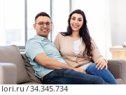happy couple sitting on sofa at home. Стоковое фото, фотограф Syda Productions / Фотобанк Лори