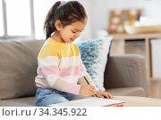 Купить «little girl drawing with coloring pencils at home», фото № 34345922, снято 7 мая 2020 г. (c) Syda Productions / Фотобанк Лори