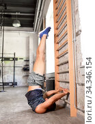 man exercising at gymnastics wall bars in gym. Стоковое фото, фотограф Syda Productions / Фотобанк Лори