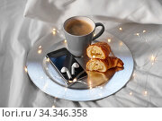 smartphone, earphones, coffee and croissant in bed. Стоковое фото, фотограф Syda Productions / Фотобанк Лори