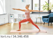 woman doing yoga warrior pose at home. Стоковое фото, фотограф Syda Productions / Фотобанк Лори