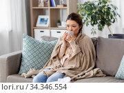 sad sick asian woman drinking hot tea at home. Стоковое фото, фотограф Syda Productions / Фотобанк Лори