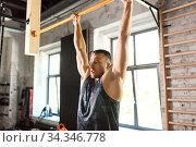 Купить «man exercising on bar and doing pull-ups in gym», фото № 34346778, снято 3 июля 2020 г. (c) Syda Productions / Фотобанк Лори