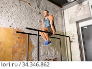 man flexing abs on parallel bars in gym. Стоковое фото, фотограф Syda Productions / Фотобанк Лори