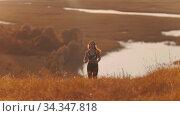Young woman jogging on the field on bright sunset. Стоковое видео, видеограф Константин Шишкин / Фотобанк Лори