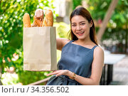 Portrait of attractive and smile asian woman holding grocery bag buy... Стоковое фото, фотограф Zoonar.com/Vichie81 / easy Fotostock / Фотобанк Лори