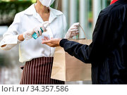 Waitress spraying alocohol on hand of deliverly man before give bakery... Стоковое фото, фотограф Zoonar.com/Vichie81 / easy Fotostock / Фотобанк Лори