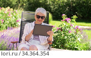 happy senior woman with tablet pc at summer garden. Стоковое видео, видеограф Syda Productions / Фотобанк Лори