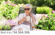 happy senior woman drinking coffee at garden. Стоковое видео, видеограф Syda Productions / Фотобанк Лори