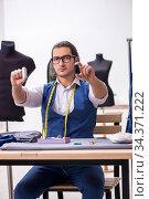 Купить «Young male tailor working at workshop», фото № 34371222, снято 6 декабря 2019 г. (c) Elnur / Фотобанк Лори