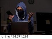 Male hacker hacking security firewall late in office. Стоковое фото, фотограф Elnur / Фотобанк Лори