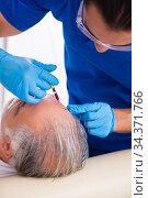 Купить «Old man visiting young male doctor in hair transplantation conce», фото № 34371766, снято 3 октября 2019 г. (c) Elnur / Фотобанк Лори