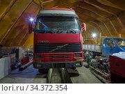 Старый грузовик Вольво FH12  на ремонте в ангаре грузового автосервиса. Редакционное фото, фотограф Виктор Карасев / Фотобанк Лори