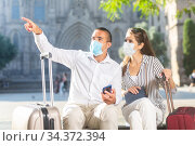 Couple of travelers in medical masks pointing at sights in foreign city. Стоковое фото, фотограф Яков Филимонов / Фотобанк Лори