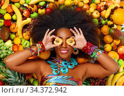 African American woman smiles closing her eyes with apricots. Стоковое фото, фотограф Алексей Кузнецов / Фотобанк Лори