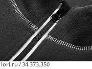 Zipper of a black fleece jacket, close-up. Стоковое фото, фотограф EugeneSergeev / Фотобанк Лори