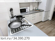 Modern white and black kitchen, gas stove with cooking pan, minimalistic... Стоковое фото, фотограф Zoonar.com/Serghei Starus / easy Fotostock / Фотобанк Лори