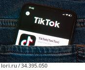 """Логотип TikTok (""""ТикТок"""") на экране мобильного телефона, лежащего в кармане джинсов (крупным планом) Редакционное фото, фотограф E. O. / Фотобанк Лори"""