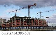 Quick motion of multi-storey under construction building and construction crane on the background of cloudy blue sky. Стоковое видео, видеограф Алексей Кузнецов / Фотобанк Лори