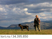 A woman in a hat with a dog of the Cane Corso breed stands on a meadow in a beautiful landscape with a view of the mountains and clouds on a summer day. Стоковое фото, фотограф Яна Королёва / Фотобанк Лори