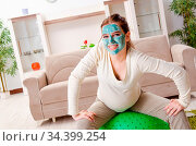 Young pregnant woman doing exercises at home. Стоковое фото, фотограф Zoonar.com/Elnur Amikishiyev / easy Fotostock / Фотобанк Лори