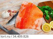 Uncooked fillet salmon fish with parsley and garlic on table. Стоковое фото, фотограф Яков Филимонов / Фотобанк Лори