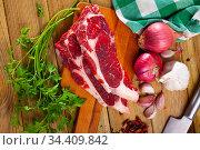 Uncooked beef fillet with parsley and garlic on table. Стоковое фото, фотограф Яков Филимонов / Фотобанк Лори