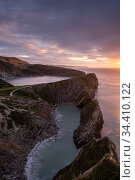 Stair Hole at sunrise, Lulworth Cove, showing 'Lulworth Crumple' strata (folded limestone), Dorset, UK. November. Стоковое фото, фотограф Ross Hoddinott / Nature Picture Library / Фотобанк Лори